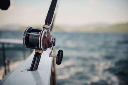Boot Angelruten über einen schönen bewölkten Seestück horizontal Standard-Bild - 51943644