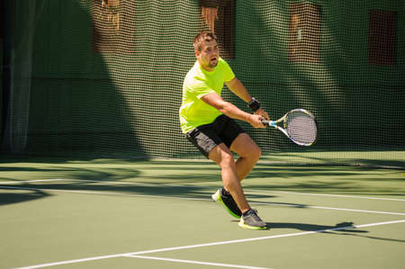 raquet: Man plays tennis in bright cloth  on  the court