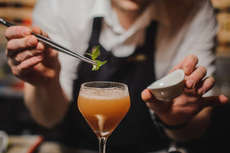 steel bar: Barman is decorating cocktail with rocket no face