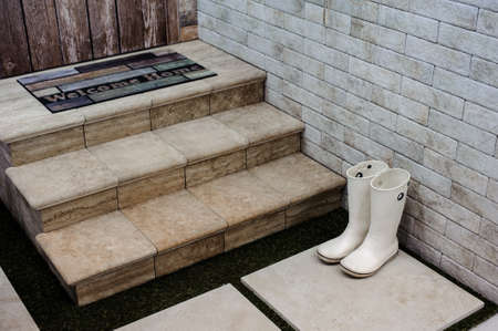 homecoming: rubber Boots on a doorstep horizontal photo Stock Photo