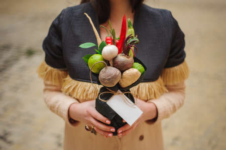 unusual vegetables: The original unusual edible bouquet of vegetables and fruits in girl hands  with card