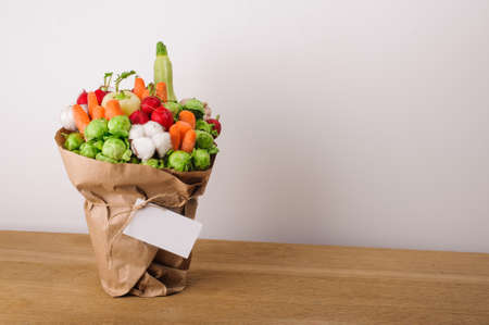 unusual vegetables: The original unusual edible bouquet of vegetables and fruits on  wood with card