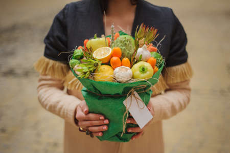 unusual vegetables: The original unusual edible bouquet of vegetables and fruits in woman hands  with card Stock Photo