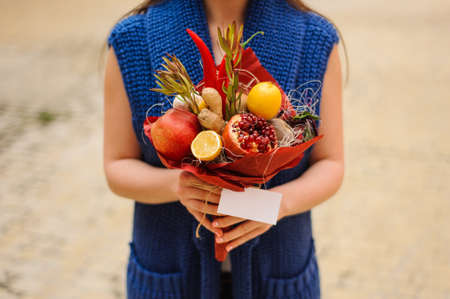 unusual vegetables: The original unusual edible bouquet of vegetables and fruits in woman hands with card