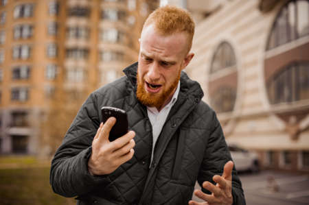 man screaming: Angry ginger man screaming on phone outdoor
