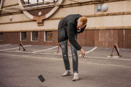 매우 화가 남자가 자신의 휴대 전화를 멀리 던지고 스톡 콘텐츠