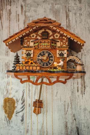eine antike Kuckucksuhr an der Wand hängen