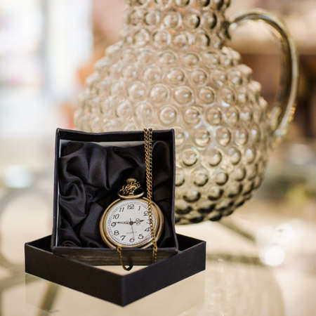 duration: Black box with golden pocket watch on chain