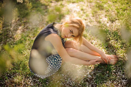 Pretty blond girl sitting on the grass in park