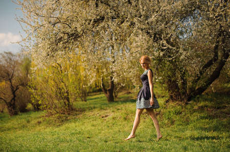 young adult woman: Young blond girl wearing dress walking barefoot in park Stock Photo