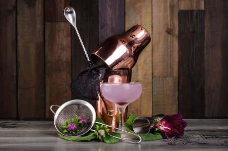 Set of bar accessories and ingredients for making a cocktails arranged on a wooden background with flowers