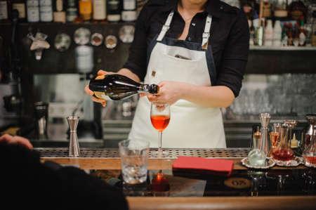bebidas alcohÓlicas: Bartender pouring champagne into glass, close-up no face