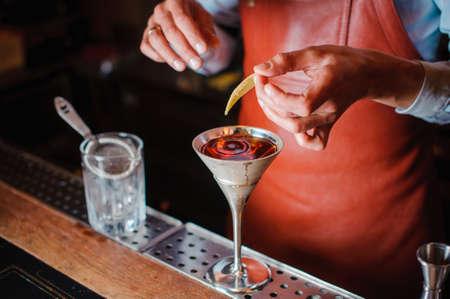 barman: Barman is finishing up cocktail with lemon no face Stock Photo