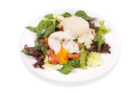 buttery: Eggs Benedict- toasted English muffins, salmon, poached eggs, and delicious buttery hollandaise sauce on salad isollated Stock Photo