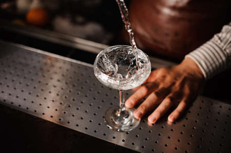 bartending: Barman pouring , splashing cocktail into a champagne glass and making a splash. no face Stock Photo