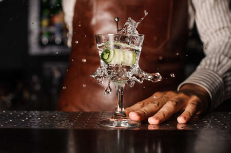 barman: cucumber falling into the glass. barman on background