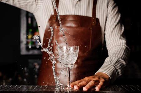 Wasser spritzt aus dem Glas infront Barmann Standard-Bild - 58752826
