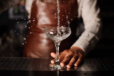 Barman pouring , splashing cocktail into a champagne glass and making a splash. no face Standard-Bild