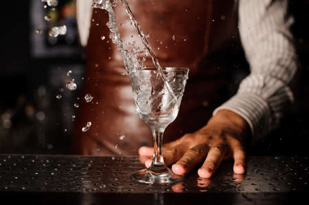 barman: Water splashes out of the glass infront of barman