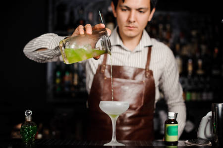 frozen glass: Barman pouring a cocktail into a frozen glass