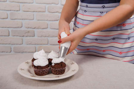 pastry bag: pastry bag putting cream over cupcake no face
