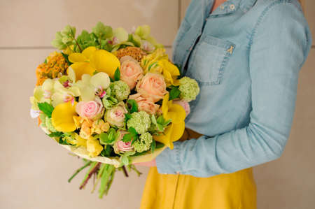 girl holding Bouquet of the different mixed orange flowers in woman hands Stock Photo
