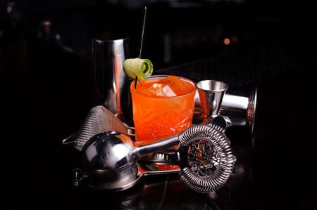 cocktail strainer: Red cocktail drink with ice. stainless steel cocktail bar tools and shaker. Stock Photo