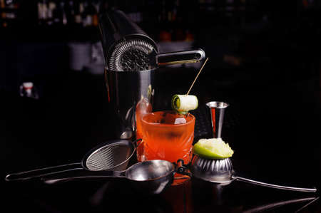 Red cocktail drink with ice. stainless steel cocktail bar tools and shaker. Stock Photo