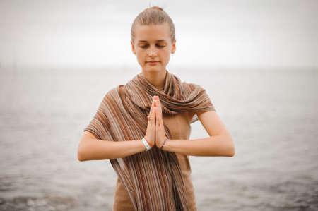 Frau steht eine dankbare namaste Yoga-Pose am Strand neben dem Ozean bei bewölktem Wetter. Standard-Bild - 60558479