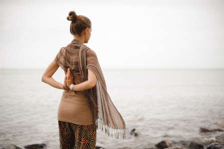 Yoga nature spa. The back of beautiful woman with her hands in namaste.