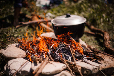 Tourist pot over the open fire. In field.