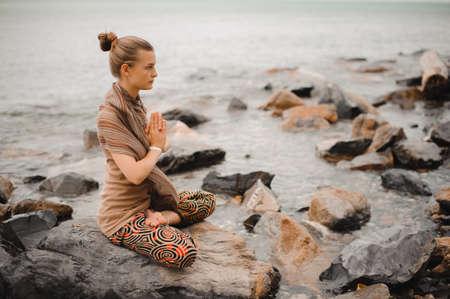 retreat: Woman meditating at the beach . yoga retreat. namaste in a lotus pose Stock Photo