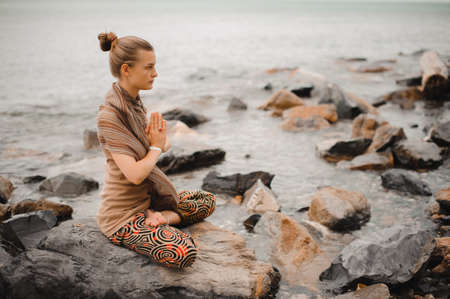 Woman meditating at the beach . yoga retreat. namaste in a lotus pose Stock Photo