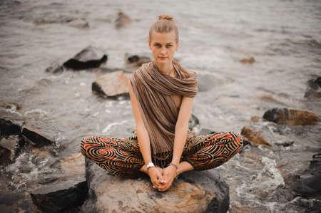 Young woman meditate on rock near sea