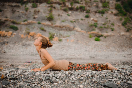 Young woman doing yoga on a rocky seashore upward facing dog pose
