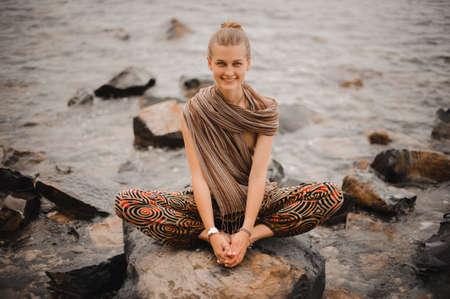 position d amour: Jeune femme m�diter sur un rocher pr�s de la mer Banque d'images