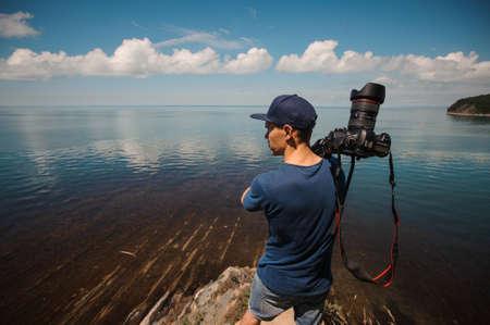 photojournalist: man photographer holding his camera. lake background Stock Photo