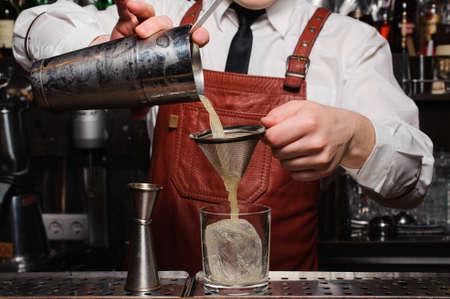 Barkeeper Gießen frischen Cocktail in fancy Glas mit Eis Standard-Bild - 60559200