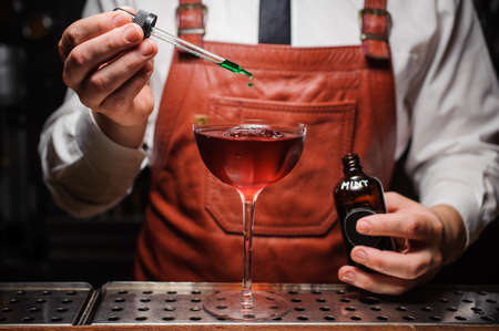 adding: Expert barman is making cocktail and finishing up by dropping green bitter