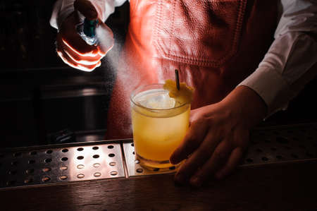 no face: Expert barman is spraying on cocktail no face