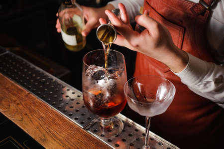 shooter drink: Barman pouring hard spirit into glass in detail. no face