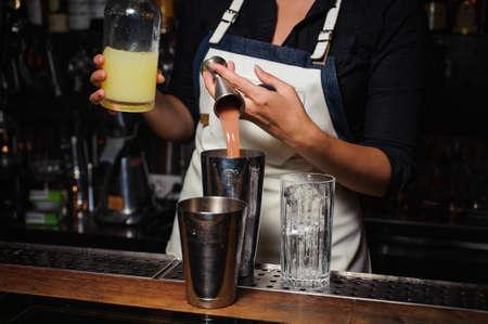 barman: Barman is making cocktail at the bar