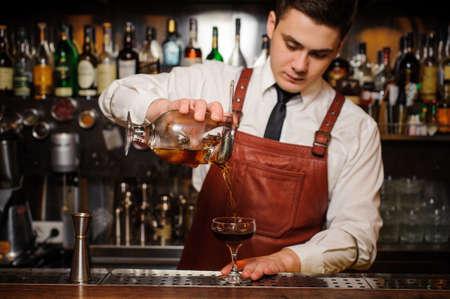 Barman gieten frisse cocktail in fancy glas met ijs Stockfoto
