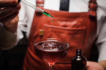 experto barman está haciendo cóctel y terminando por dejar caer verde amargo