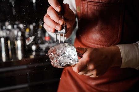 barman: barman breaking ice with pick behind bar Stock Photo