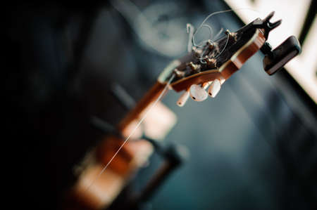 six-string acoustic guitar on a stand on stage Stock Photo