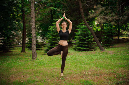 Practicing yoga with trees Attractive young caucasian woman standing in yoga tree pose on the grass.