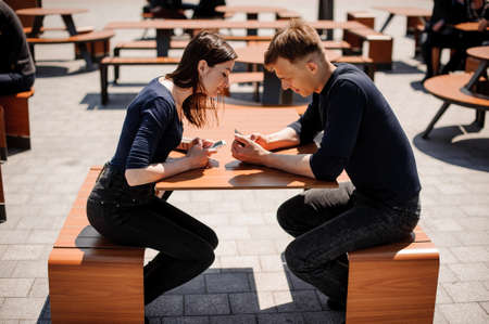 cheater: Secretive Couple with Smart Phones in Their Hands Young adult couple has privacy problems with modern technology