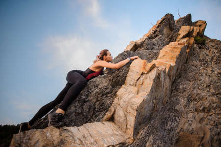 crack climbing: Female extreme climber conquers the steep rocks Stock Photo