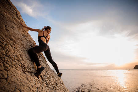 conquers: Female extreme climber conquers steep rock against the sunset over the river.